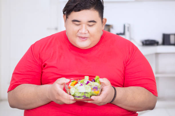 Happy fat man holding salad in the kitchen stock photo