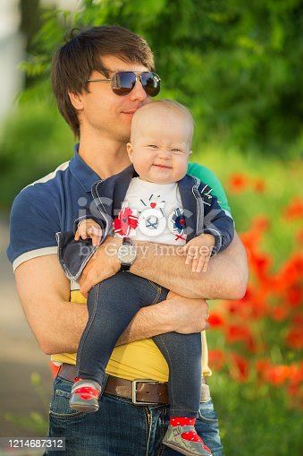 480122543 istock photo Happy father and child playing together on the poppy meadow. 1214687312
