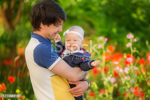 480122543 istock photo Happy father and child playing together on the poppy meadow. 1214689167