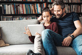 happy father and daughter at sofa looking at digital tablet