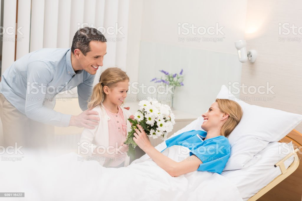 happy father and daughter bringing flowers to sick woman stock photo