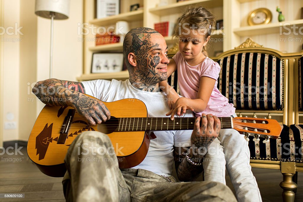 Happy father and daughter playing acoustic guitar at home. stock photo