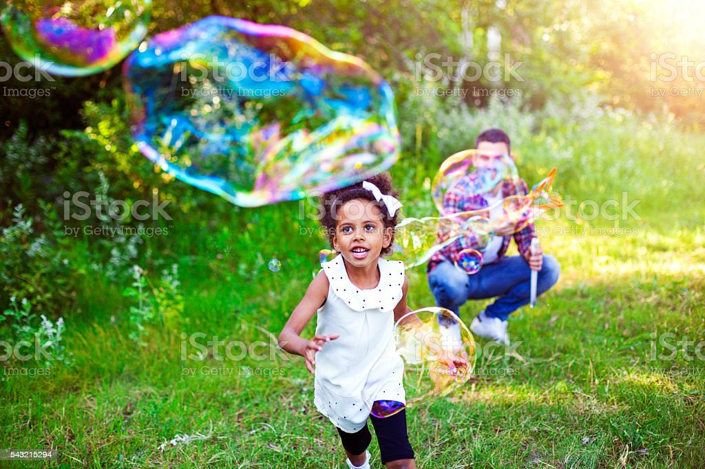 Happy Father And Daughter Playing Soap Bubbles In Park