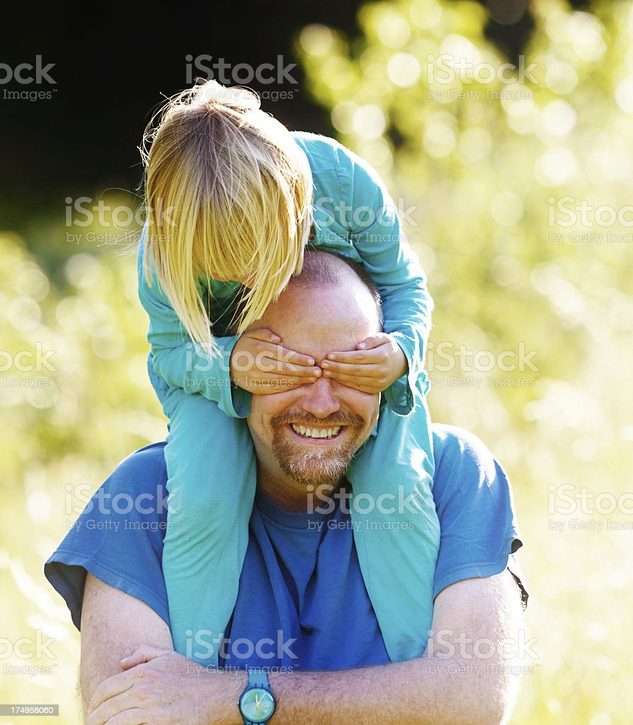 Happy father and daughter playing together in meadow stock photo