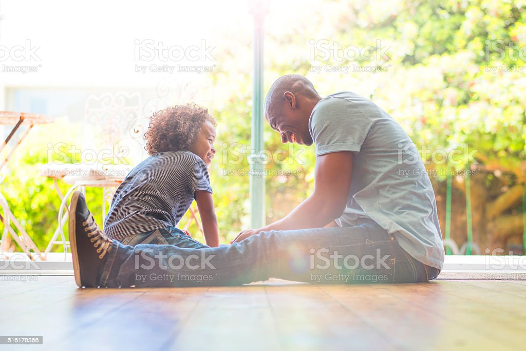 Happy father and daughter sitting on floor at home stock photo