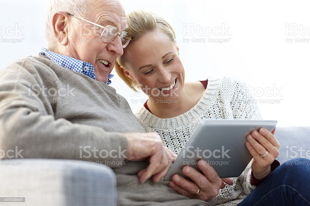 Happy father and daughter using digital tablet at home stock photo