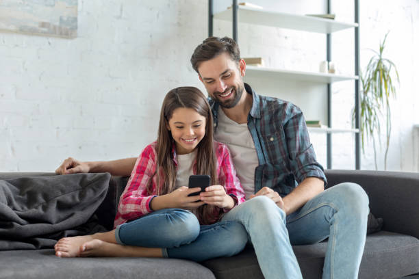 Happy father and daughter using phone together stock photo