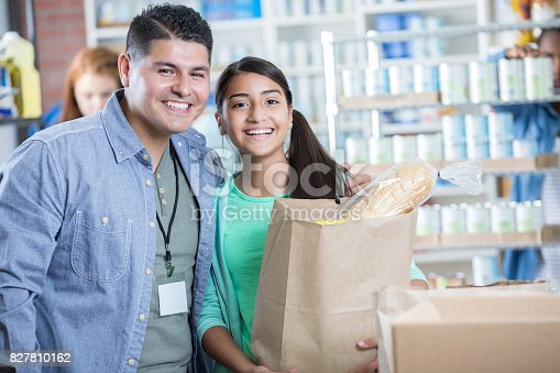 istock Happy father and daughter volunteer in community food bank 827810162