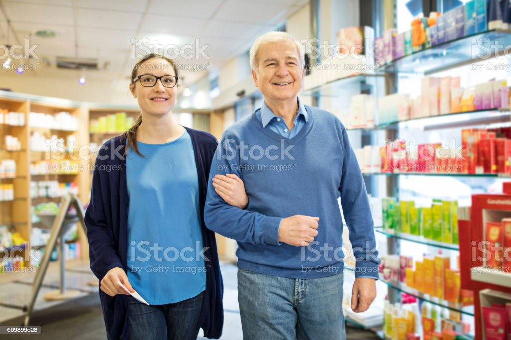 Happy father and daughter walking at pharmacy stock photo