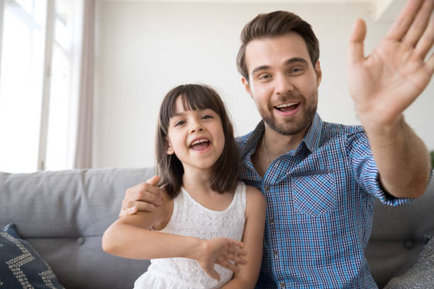 Happy father and daughter wave hands looking at camera Head shot portrait of cheerful smiling diverse family looking at camera. Young male sitting on couch at home with daughter have video call using computer, wave hands greeting or say goodbye to friend young girls on webcam stock pictures, royalty-free photos & images