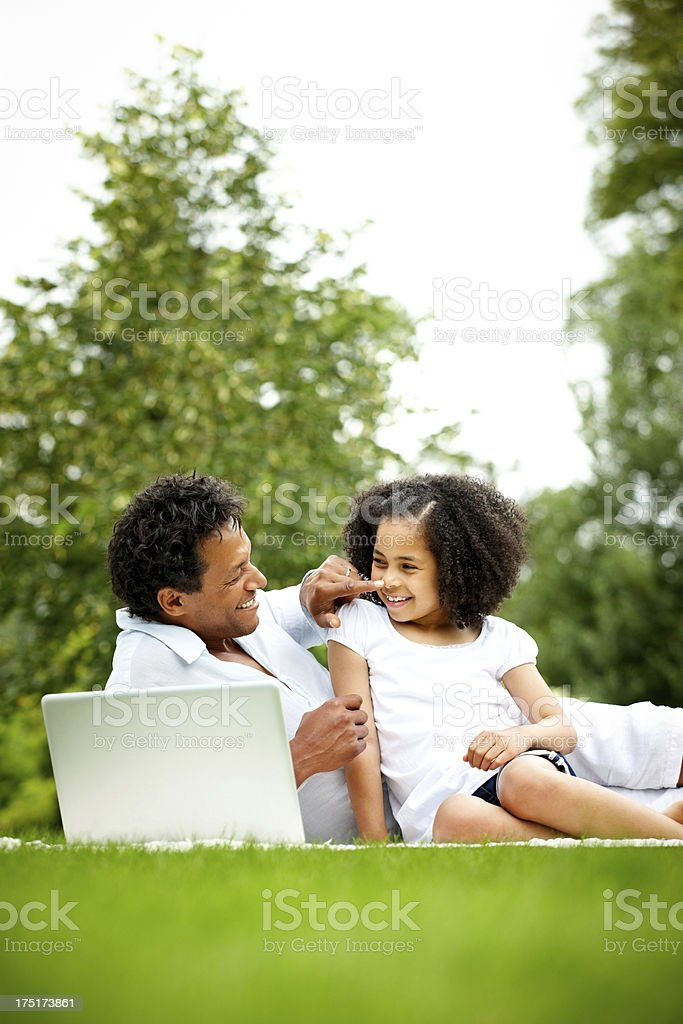 Happy father and daughter with a laptop in park stock photo