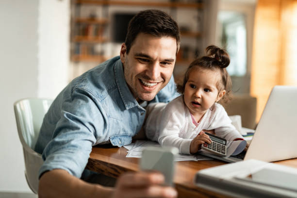 Happy father and his small daughter taking selfie with mobile phone at home. Stay at home father having fun while working at home and taking selfie with his baby girl. stay at home father stock pictures, royalty-free photos & images