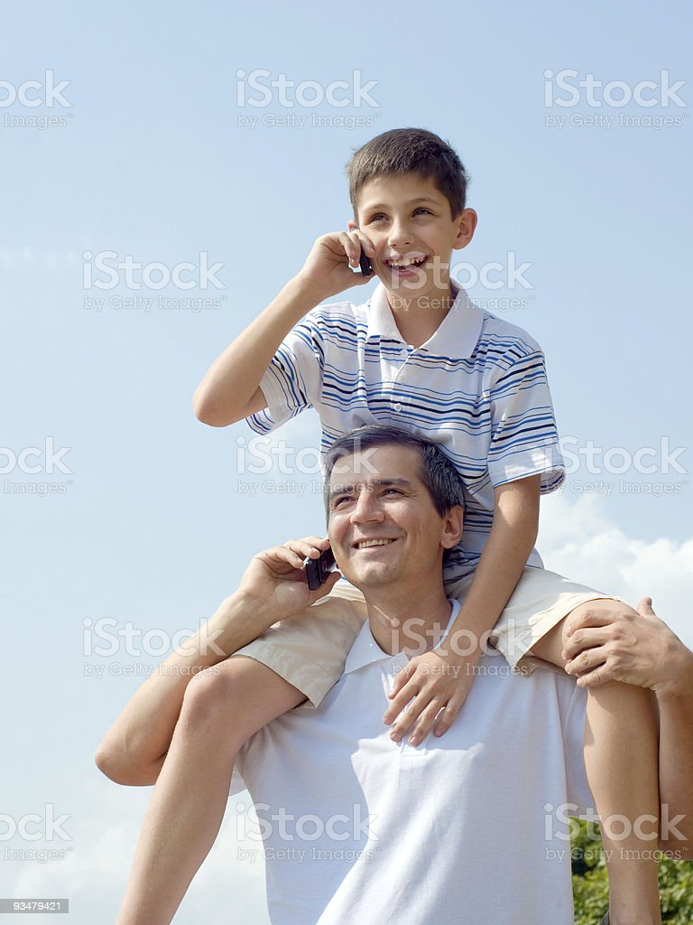 Happy father and his son are speaking over mobiles royalty-free stock photo