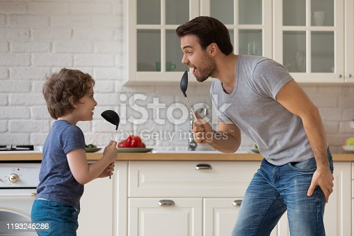 Happy father and little son playing funny game, having fun in kitchen, holding soup ladles as microphones, singing and dancing, dad and adorable boy child enjoying weekend at home together