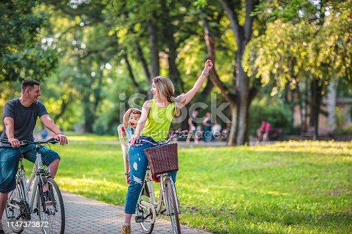 istock Happy father and mother with kid on bicycles having fun in park. 1147373872