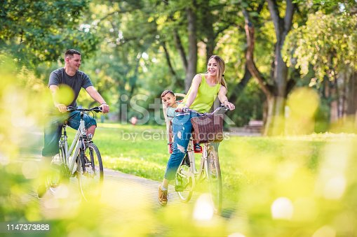 istock Happy father and mother with kid on bicycles having fun in park. 1147373888