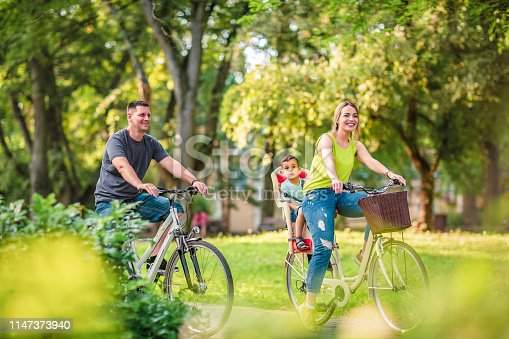istock Happy father and mother with kid on bicycles having fun in park. 1147373940