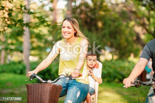 istock Happy father and mother with kid on bicycles having fun in park. 1147373992