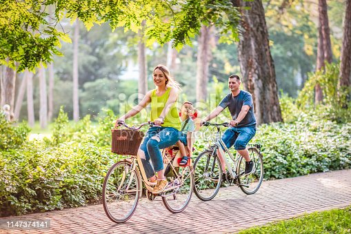 istock Happy father and mother with kid on bicycles having fun in park. 1147374141