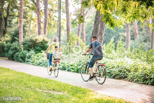 istock Happy father and mother with kid on bicycles having fun in park. 1147374175