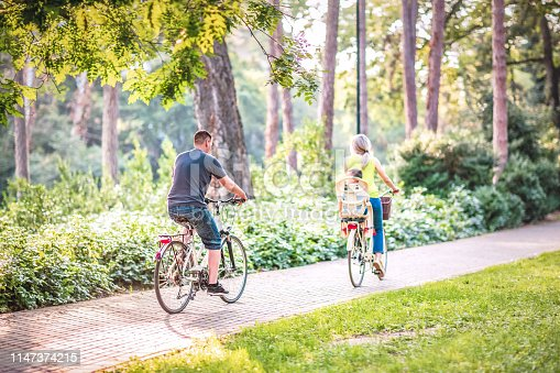 istock Happy father and mother with kid on bicycles having fun in park. 1147374215