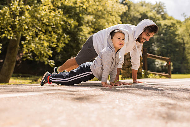 happy father and son exercising push-ups in the park. - brauns 619249228 stock-fotos und bilder