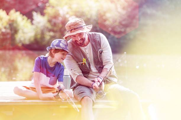 Happy father and son fishing in lake while sitting on pier stock photo