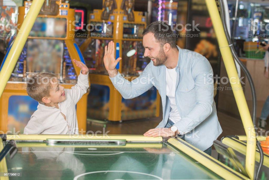 feliz pai e filho, dando cinco enquanto jogava hóquei de ar no centro de entretenimento - foto de acervo