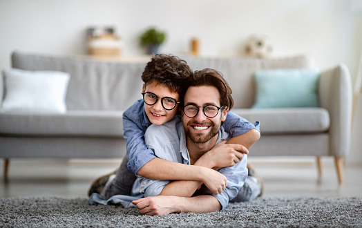 Happy father and son having fun at home. Daddy lying on carpet carrying boy on back and smiling together to camera. Parents and children being friends, single dad concept