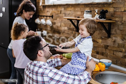 1159543952istockphoto Happy father and son having fun in the kitchen. 1185216274