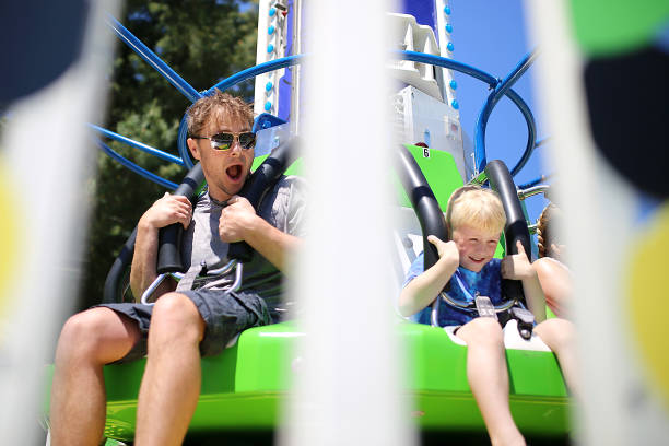 Happy Father and Son Having Fun Riding a Carnival Ride on a Summer Day stock photo