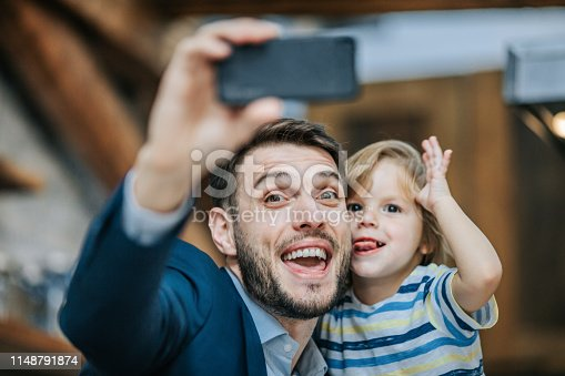 Business father and his small boy having fun while making faces and taking a selfie with smart phone. Focus is on man.