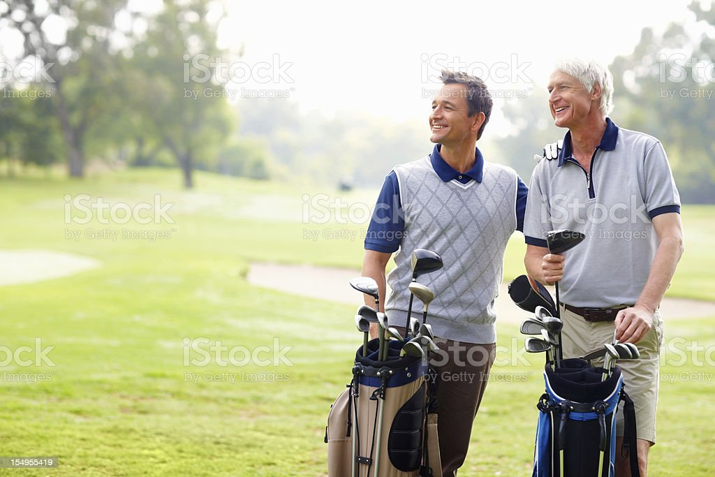 Happy father and son on a golf course stock photo
