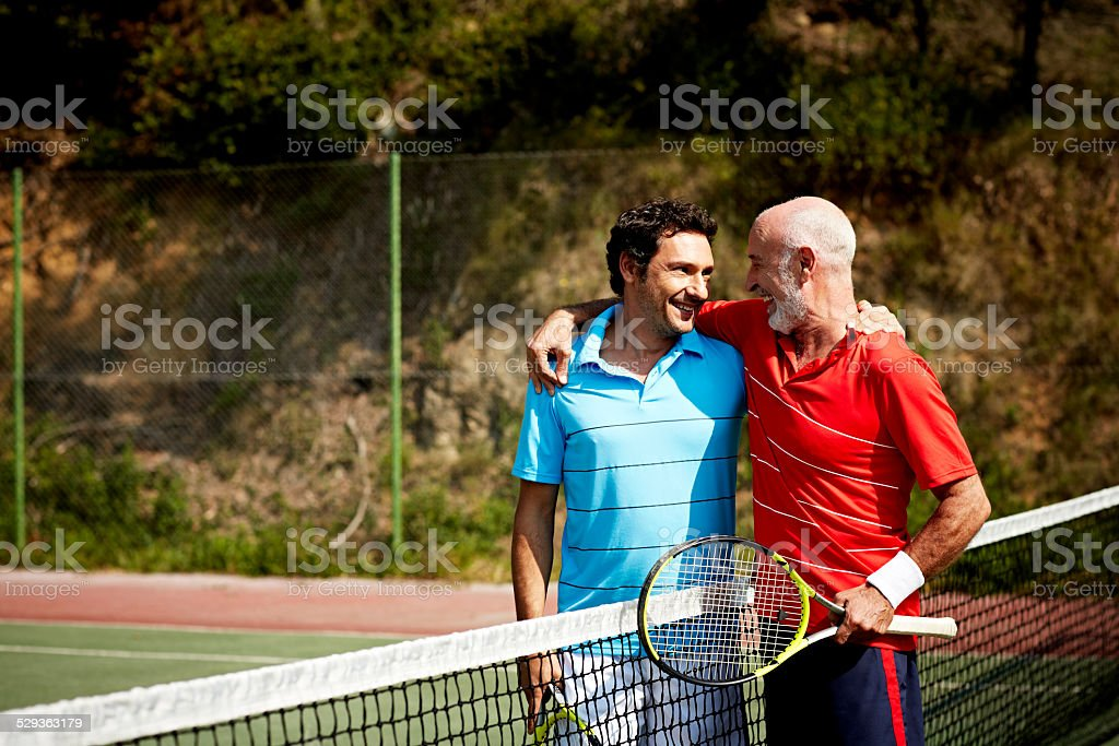 Happy father and son on tennis court stock photo