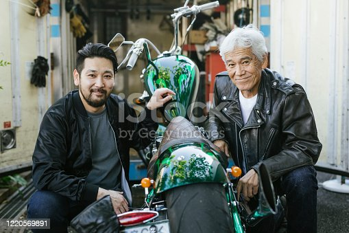 Portrait of father and son working on a motorcycle together.