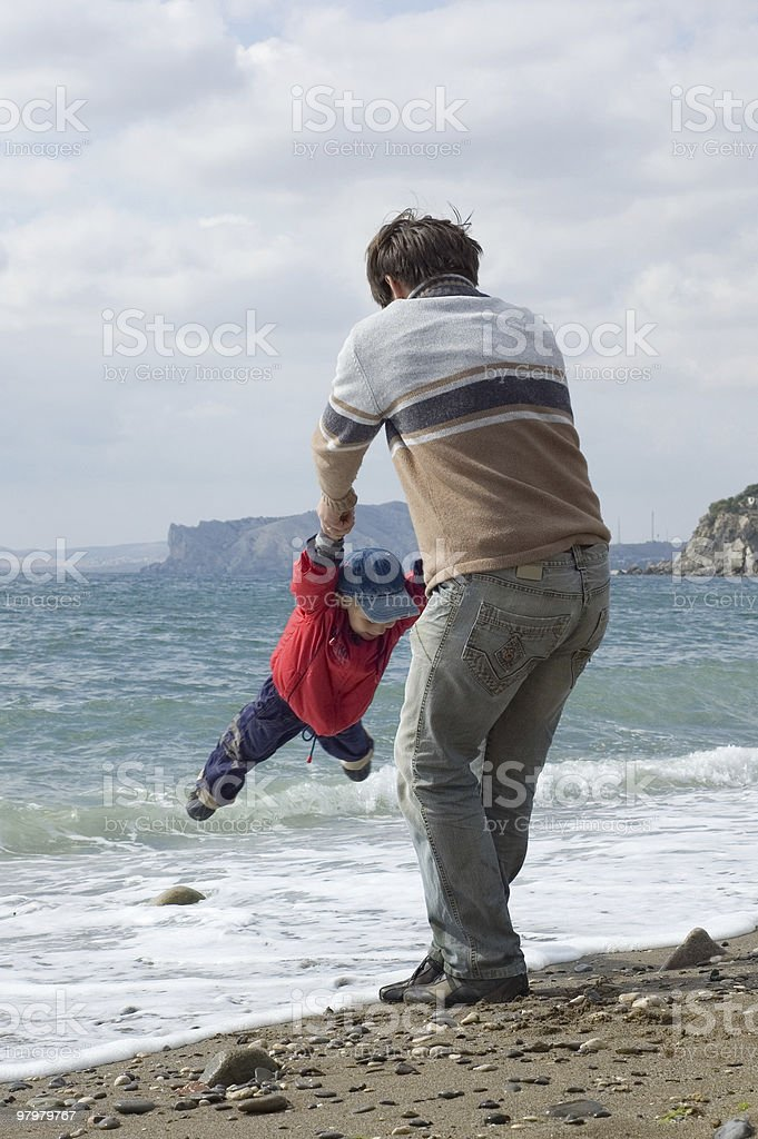 happy father and son play on the beach royalty-free stock photo