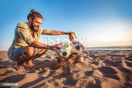 istock Happy father and son play soccer or football on the beach having great family time on summer holidays. 1058658198
