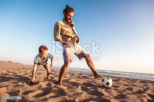 istock Happy father and son play soccer or football on the beach having great family time on summer holidays. 1125427285