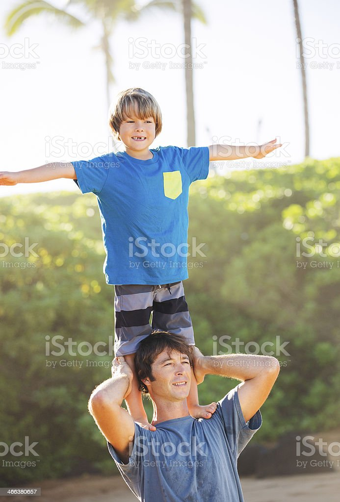 Happy father and son playing on beach stock photo
