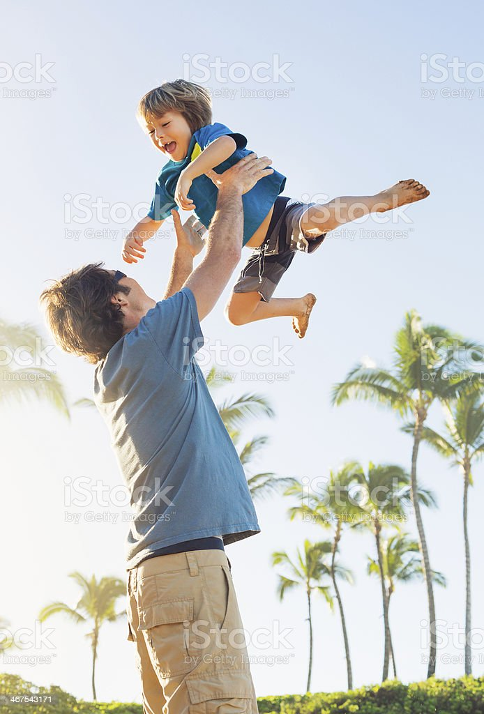 Happy father and son playing on tropical beach stock photo