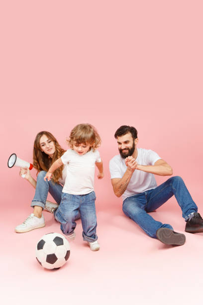 happy father and son playing together with soccer ball on pink - soccer supporter portrait imagens e fotografias de stock