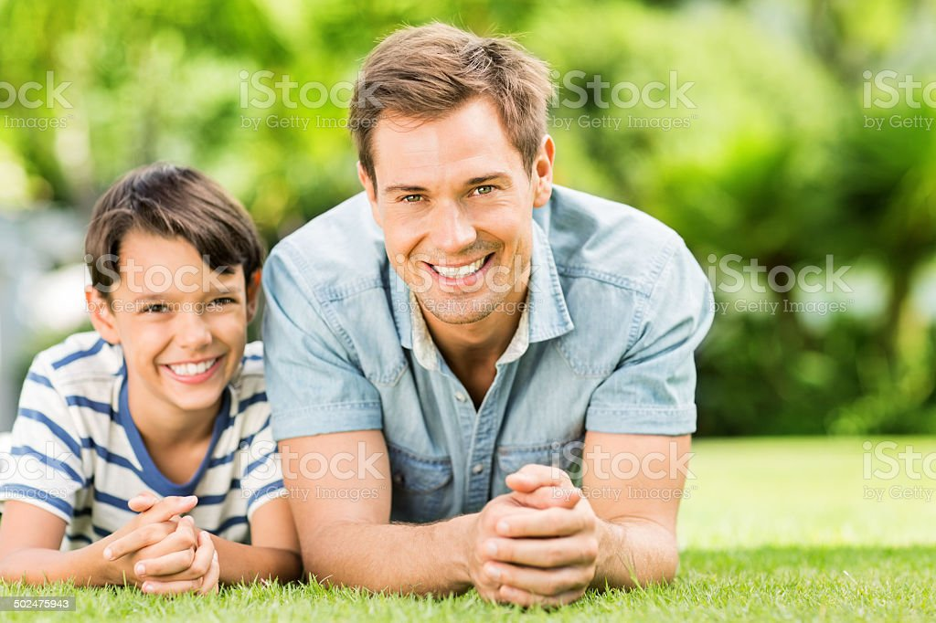 Happy Father And Son Relaxing On Grass royalty-free stock photo