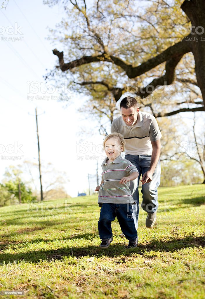 A happy father and son running and playing in a park. stock photo