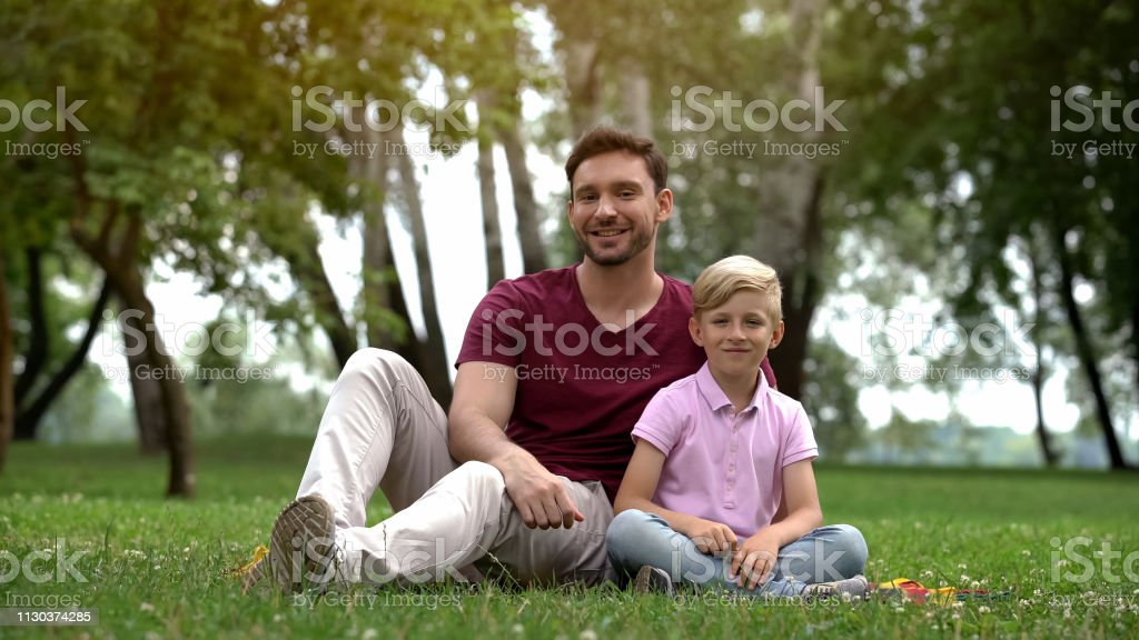 Happy father and son sitting in park, ad of social support for single...