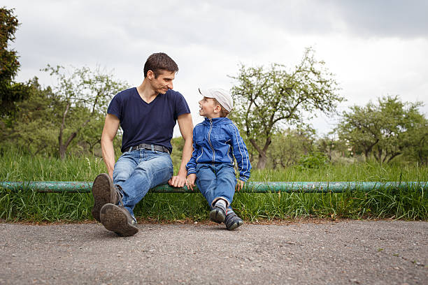 Happy father and son sitting in the park Happy father and son sitting in the park. Smiling young man spending time together with his son sergionicr stock pictures, royalty-free photos & images