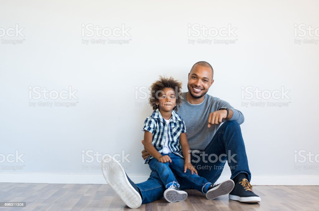 Happy father and son sitting stock photo