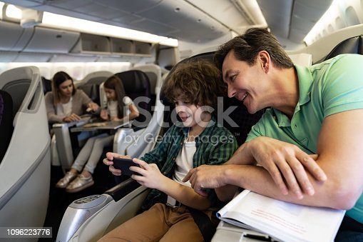 Portrait of a happy father and son traveling by plane and using a cell phone onboard - travel concepts