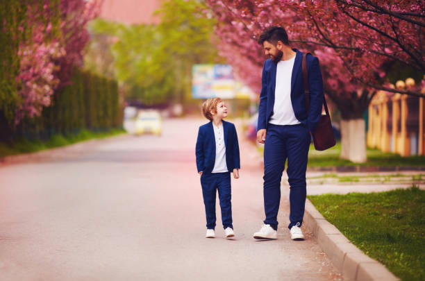 happy father and son walking together along blooming spring street, wearing suits stock photo