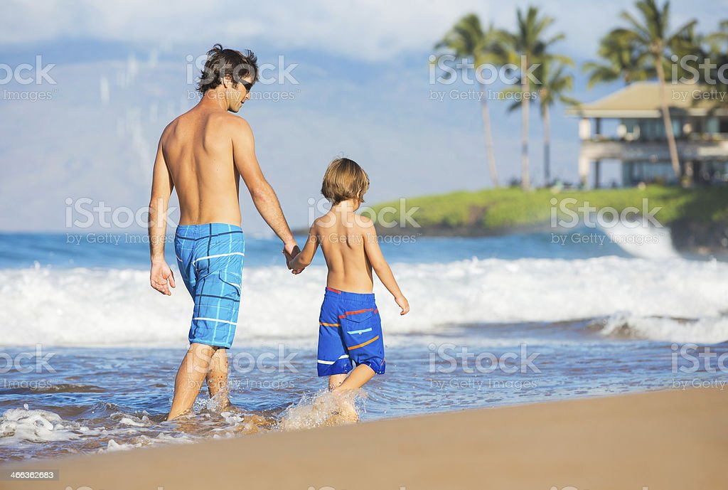 Happy father and son walking together at beach stock photo