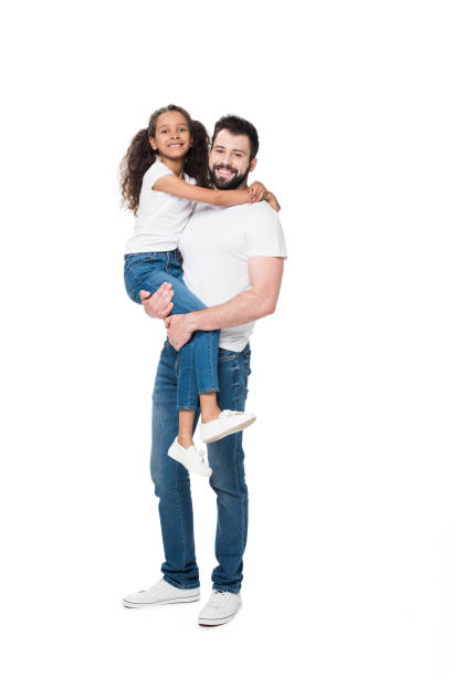 Happy father carrying adorable little daughter and smiling at camera stock photo